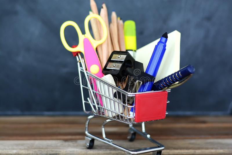 Förbereda sig för skolan - shoppingvagn med skolatillförsel över den svart tavlan arkivbilder