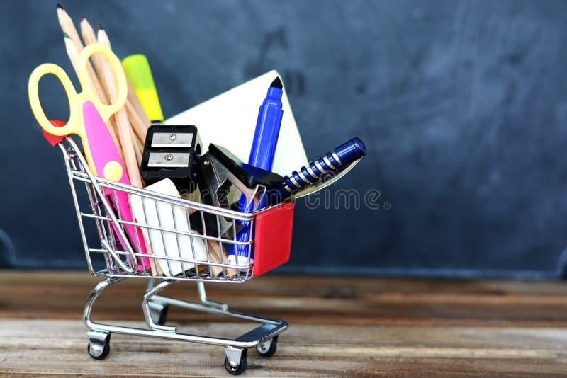 Förbereda sig för skolan - shoppingvagn med skolatillförsel över den svart tavlan fotografering för bildbyråer