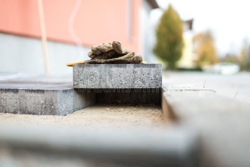 Förberedande sten som vilar ovanför nyligen installerade tegelstenar fotografering för bildbyråer