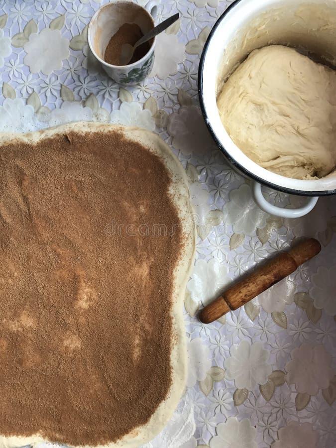 Förberedelse av bullar med kanelbrunt hemmastatt Magasinet strilas med mjöl, deg och en träkavellögn på tabellen royaltyfri bild