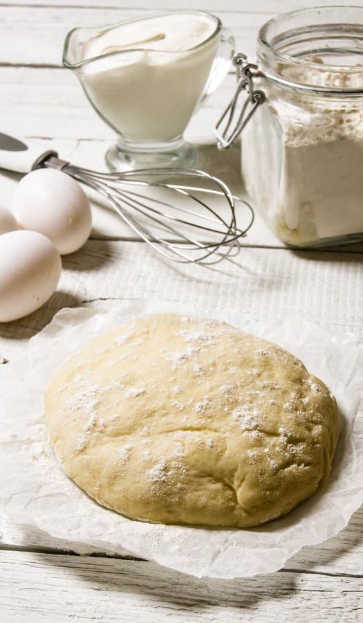 Förberedelse av degen Den förberedda degen med ingredienserna - ägg, mjöl, gräddfil och viftar arkivfoton
