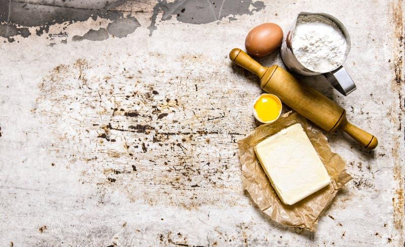 Förberedelse av degen Ingredienser för degen - mjöl, ägg, smör med en kavel arkivfoto