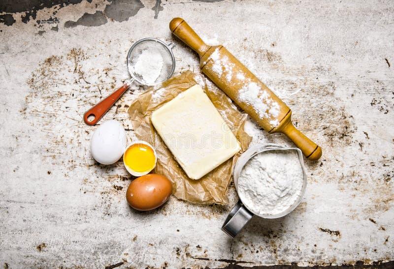 Förberedelse av degen Ingredienser för degen - mjöl, ägg, smör med en kavel royaltyfri fotografi