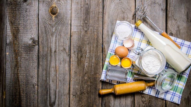 Förberedelse av degen Ingredienser för degen - mjölka, ägg, mjöl på torkduken arkivfoto