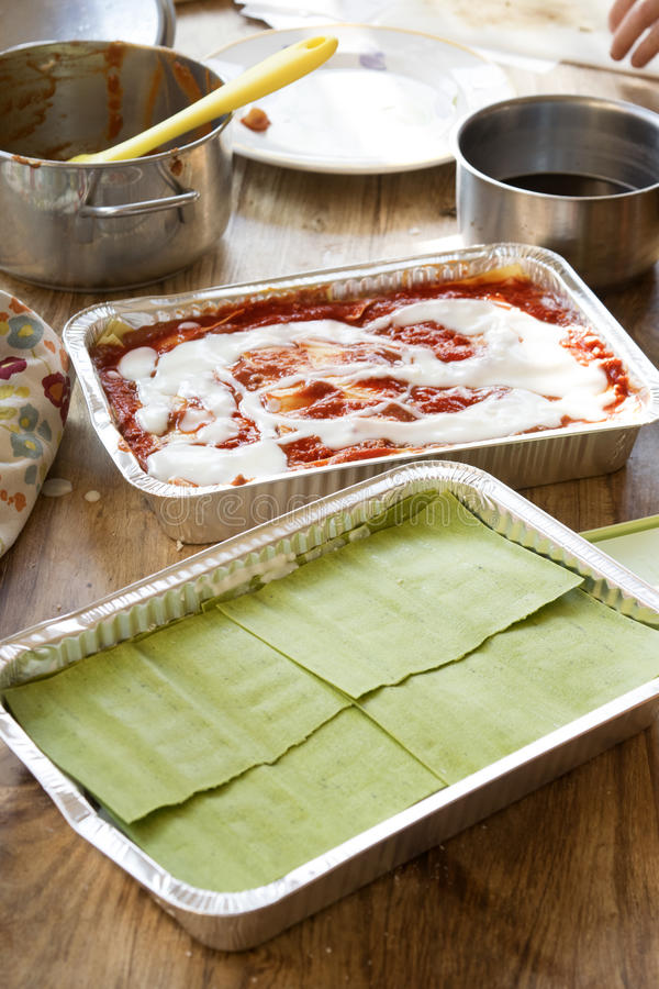 Förberedelse av den gröna och klassiska lasagnen fotografering för bildbyråer