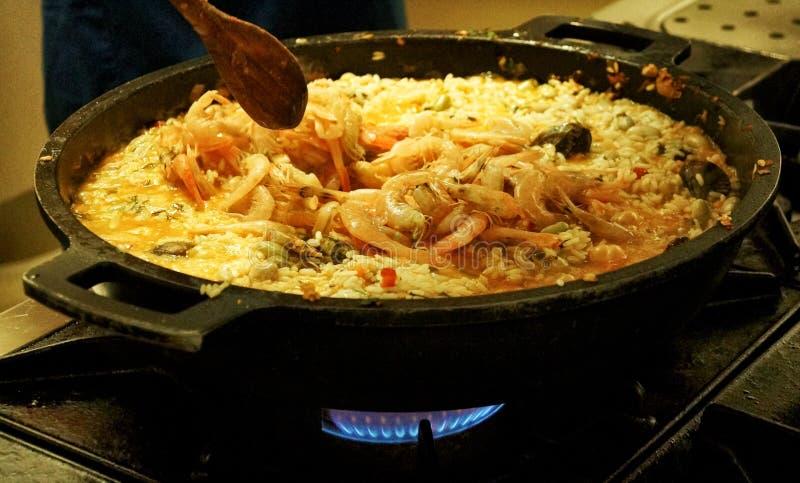 Förberedelse av den spanska traditionella maträtten - paella arkivfoto
