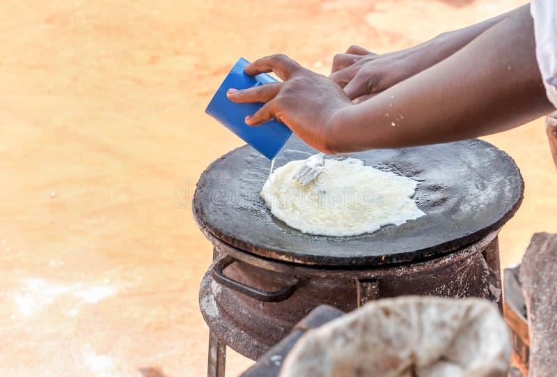 Förberedelse av den traditionella ugandiska frukosten Rolex som göras med cha arkivfoton