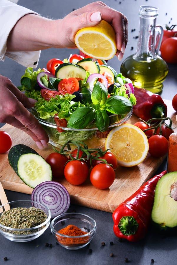 Förberedelse av en grönsaksallad från nya organiska ingredienser royaltyfri fotografi
