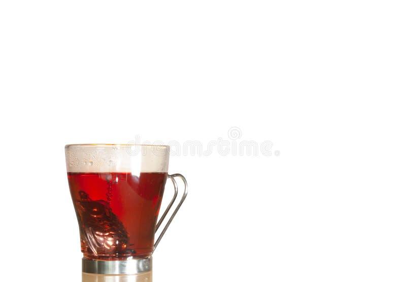 Förberedelse av Jamaica Tea med en individuell silverteapot som är nedsänkt i den genomskinliga glasbägaren royaltyfri foto
