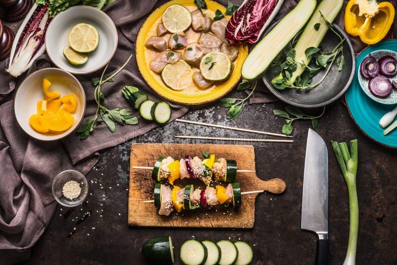 Förberedelse av olika hemlagade fega köttgrönsaksteknålar för galler eller bbq på lantlig bakgrund med ingredienser royaltyfri bild