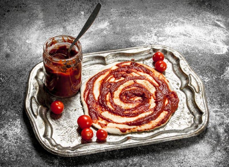 Förberedelse av pizza Applikation av tomatsås på den rullande degen royaltyfri bild