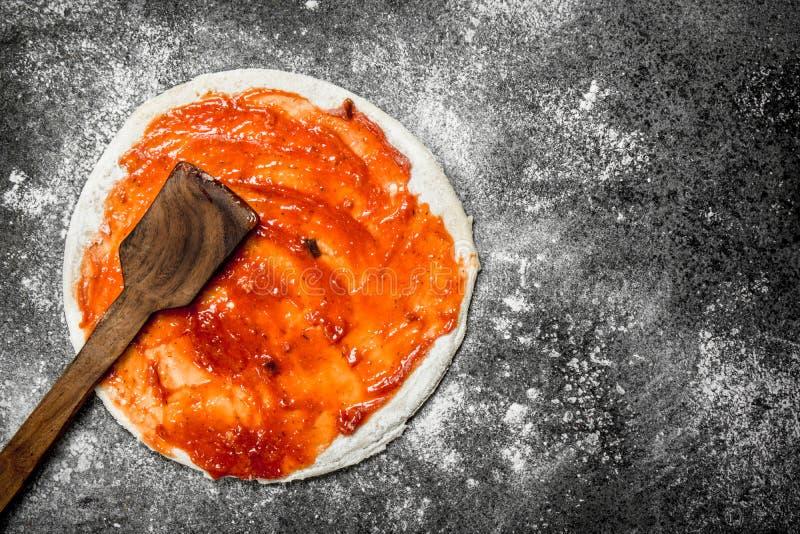 Förberedelse av pizza Applikation av tomatsås på den rullande degen royaltyfria foton
