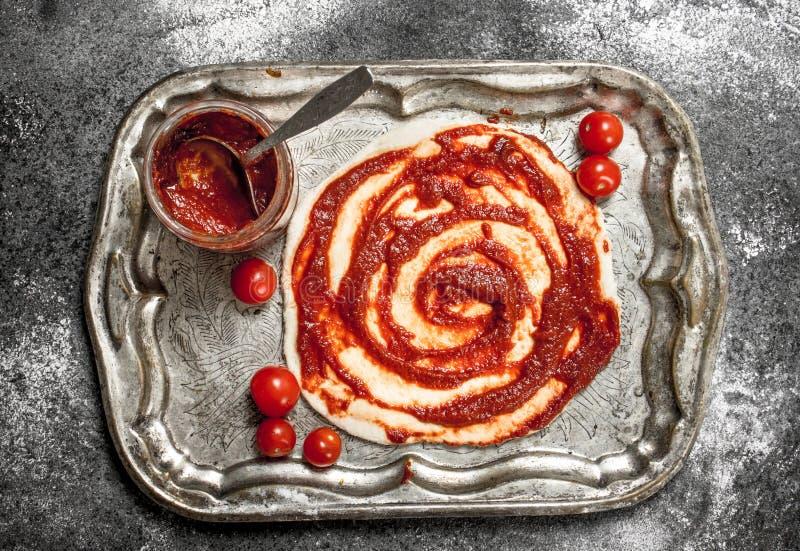 Förberedelse av pizza Applikation av tomatsås på den rullande degen arkivbilder