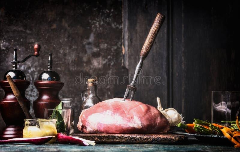 Förberedelse av rått grisköttskinkakött på det lantliga köksbordet på mörk träbakgrund arkivfoto