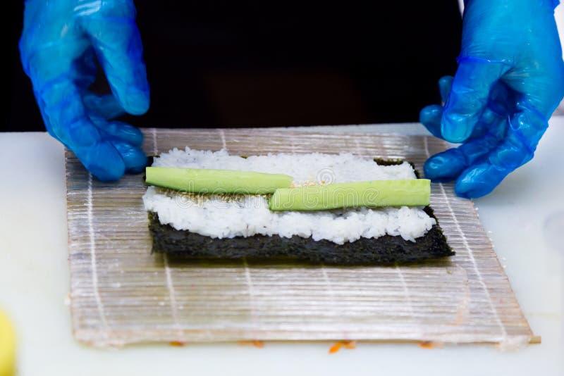 Förberedelse av rullar i en sushistång En yrkesmässig kock som bär blåa handskar, förbereder traditionell japansk mat arkivbild