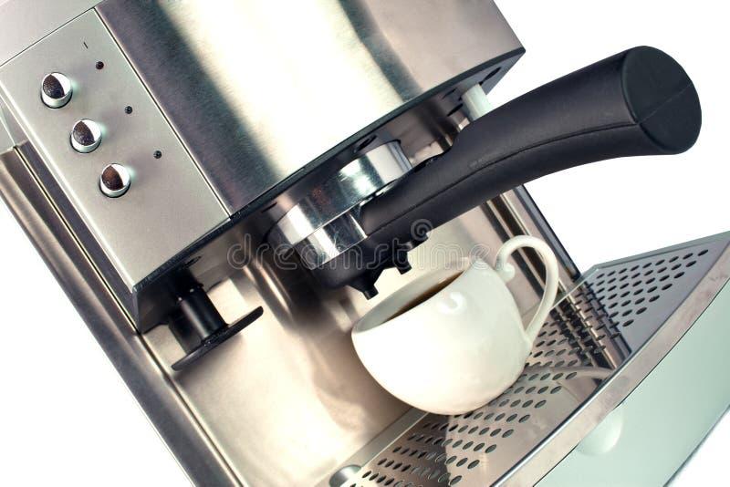 Förberedelse av svart kaffe i kaffemaskinen, ett slut upp på en vit bakgrund royaltyfri foto
