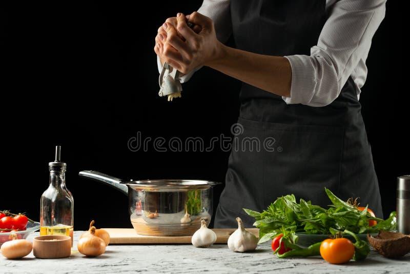 Förberedelse av tomatsås vid händerna av kocken, moment processen i köket på en svart bakgrundskopia texten av royaltyfria foton