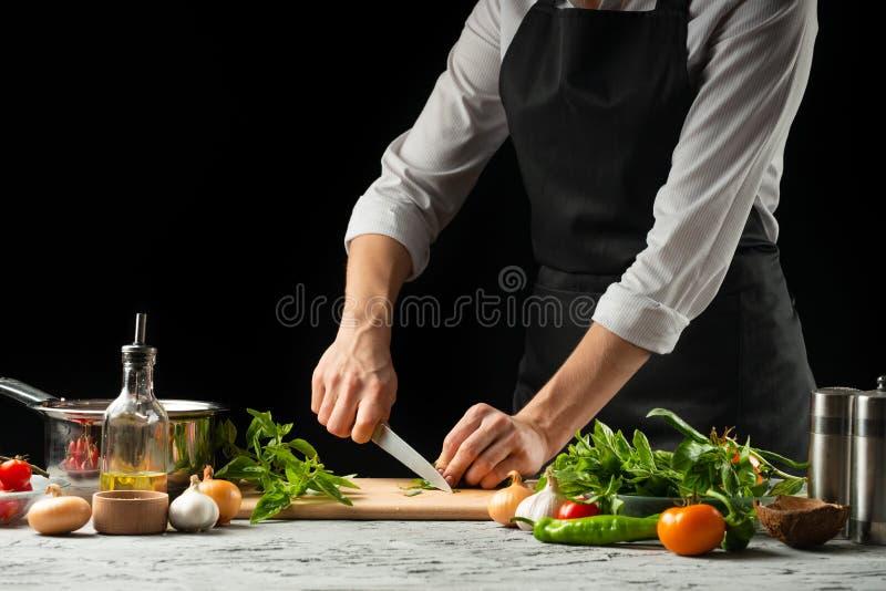 Förberedelse av tomatsås vid händerna av kocken, moment processen i köket på en svart bakgrundskopia texten av royaltyfri fotografi