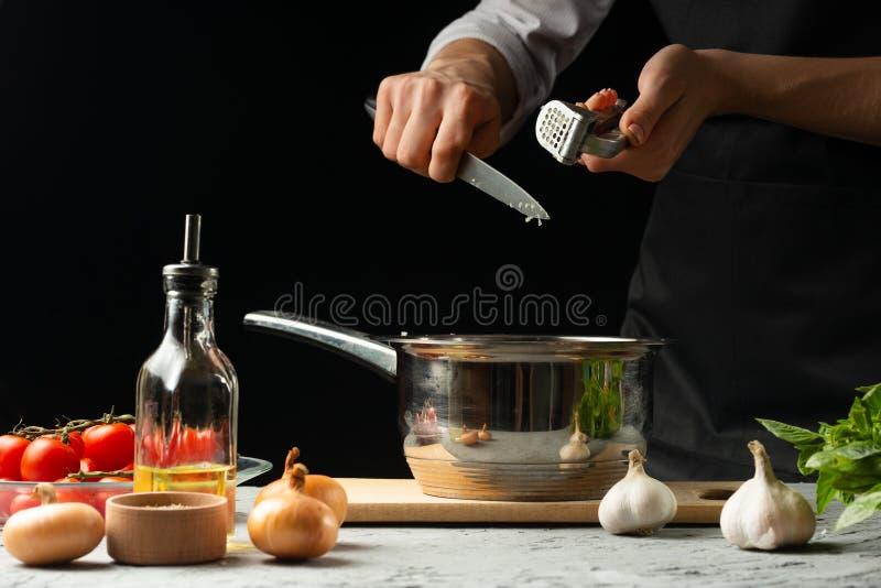 Förberedelse av tomatsås vid händerna av kocken, moment processen i köket på en svart bakgrundskopia texten av arkivfoto