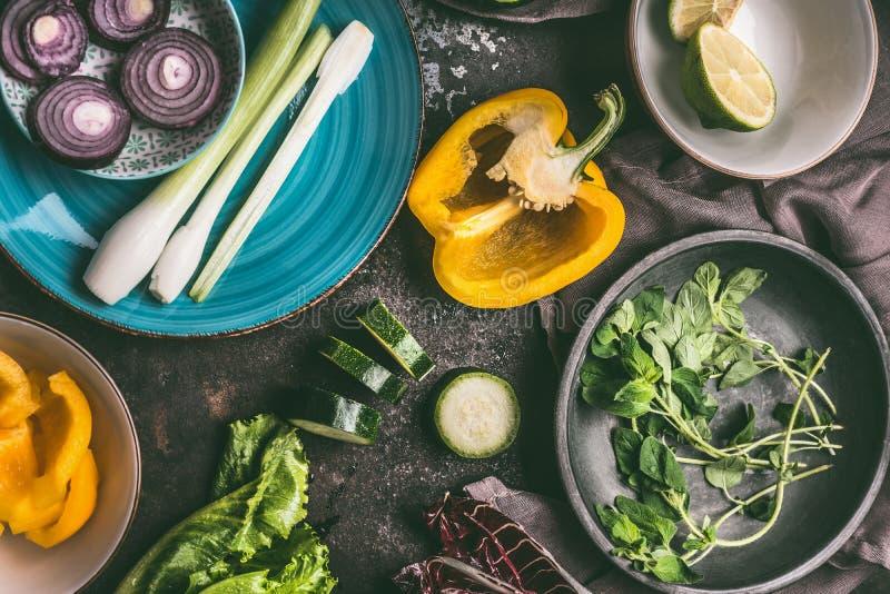 Förberedelse av vegetarisk matlagning med olika grönsaker i bunkar och plattor och smaktillsats på lantlig bakgrund, bästa sikt arkivbilder