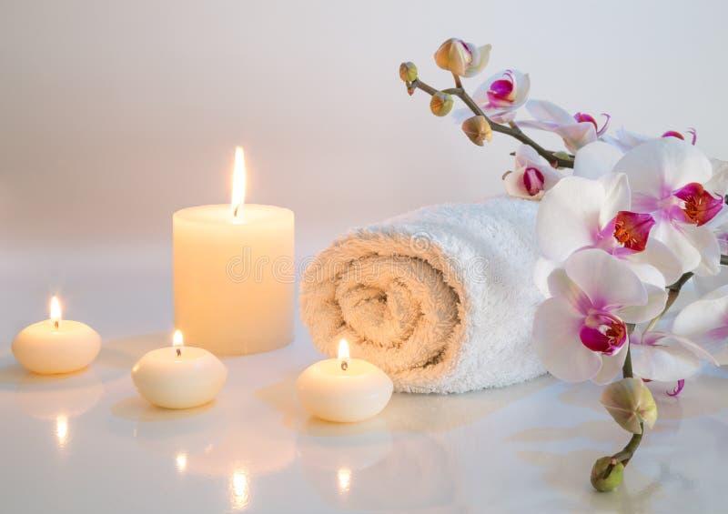 Förberedelse för bad i vit med handdukar, stearinljus och orkidén arkivbilder