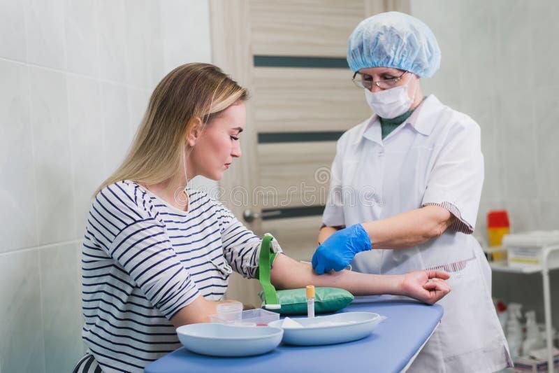 Förberedelse för blodprov med den nätta unga blonda kvinnan av den kvinnliga doktorn i medicinsk likformig för vitt lag på tabell royaltyfria bilder
