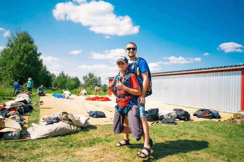 Förberedelse för hopp Två unga fallskärmshoppare förbereder sig för ett hopp arkivbild