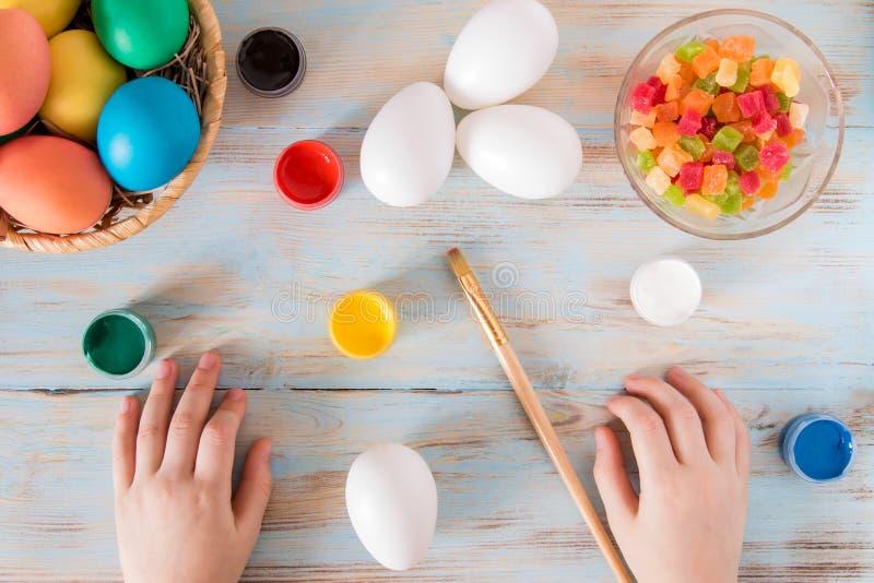 Förberedelse för påskuppsättningen för att färga ägg på rustikbakgrund med barnhänder royaltyfri foto