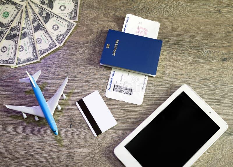 Förberedelse för resande begrepp, flygplan, bärbar dator, logipasserande, pass, kreditkort, på tappningträbakgrund arkivfoto
