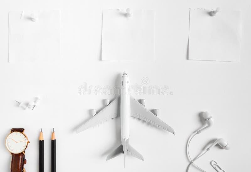Förberedelse för resande begrepp, klocka, flygplan, blyertspennor, pappers- noterat, hörlur, pushstift royaltyfria bilder