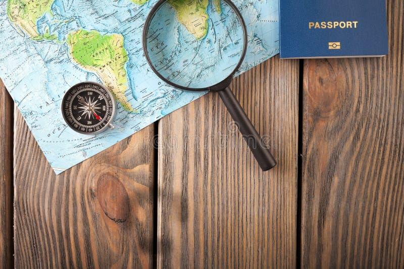 Förberedelse för resande begrepp, pass, kompass, översikt på en träbakgrund arkivfoto