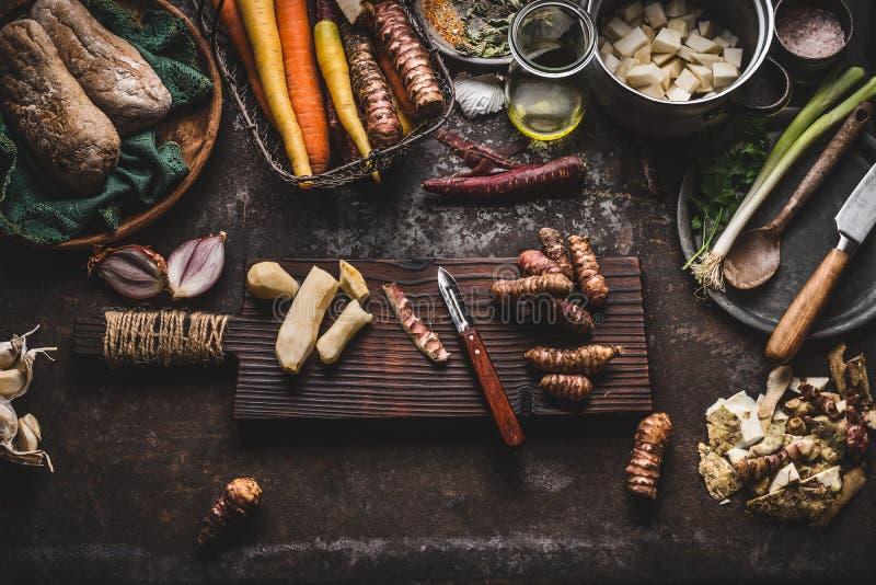 Förberedelse för skalning för Jerusalem kronärtskocka på det lantliga köksbordet med krukan, tärnade grönsaker, olja och ingredie fotografering för bildbyråer