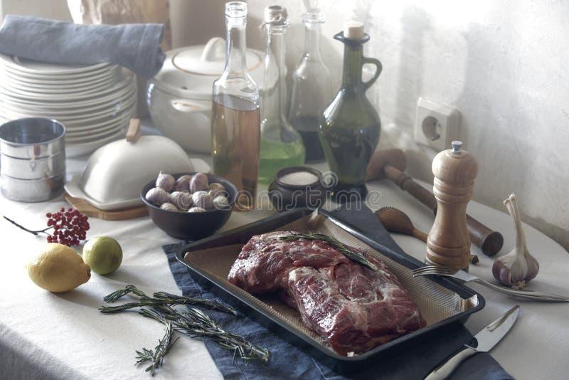 Förberedelse för stekhett kött Köksgeråd och bordsservis på arkivfoto