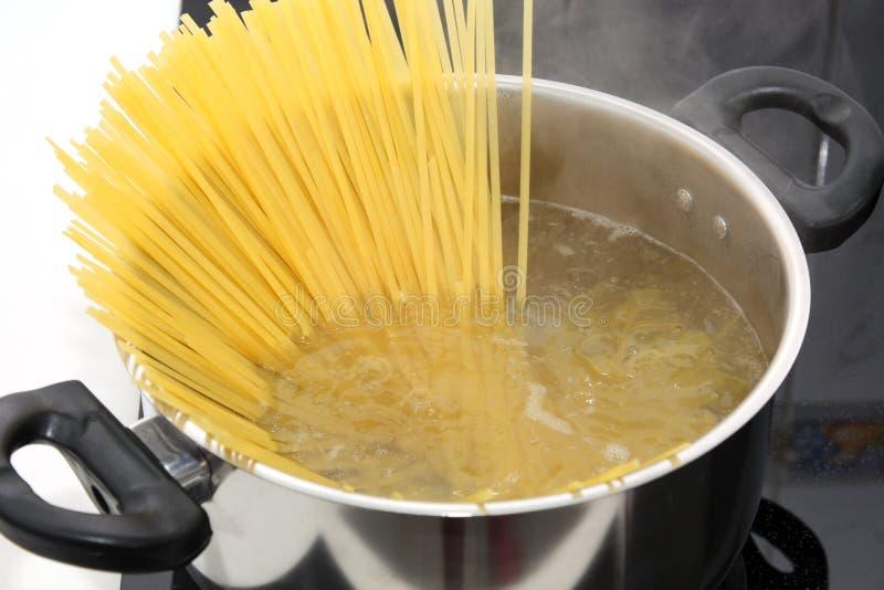 Förberedelse: pasta i kokande vatten i panna royaltyfri foto