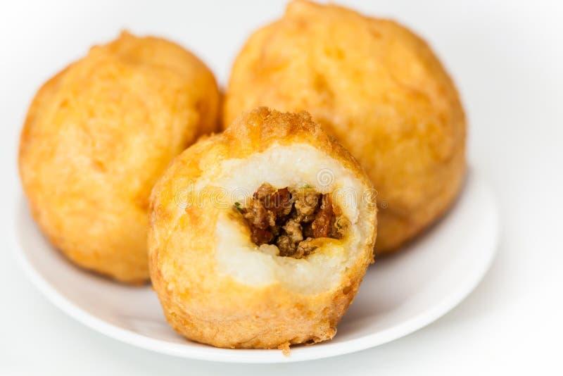 Förberedelsemoment av den traditionella colombianska maträtten kallade välfyllda potatisar arkivfoto