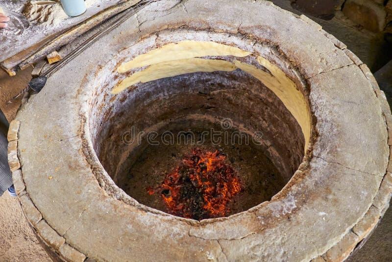 Förberedelsen av bröd i en runda stenar ugnen arkivbilder