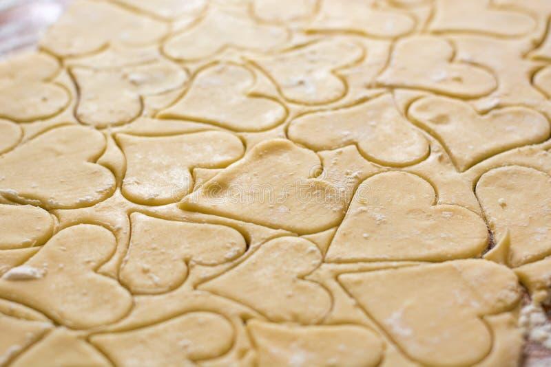 Förberedelsen av degen, rullar ut med en kavel och klippte former i form av hjärtor Stekheta kakor för ferien Close- arkivfoton