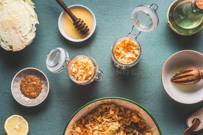 Förberedelsen av morotkålsallad i krus för sund lunch är på köksbordbakgrund, bästa sikt, med kopieringsutrymme royaltyfri foto