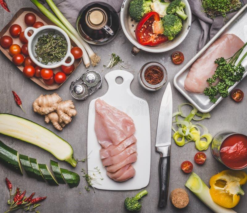 Förberedelsen för det fega bröstet med olika grönsaker och ingredienser för smakligt bantar matlagning på grå färgbetongbakgrund, royaltyfria foton