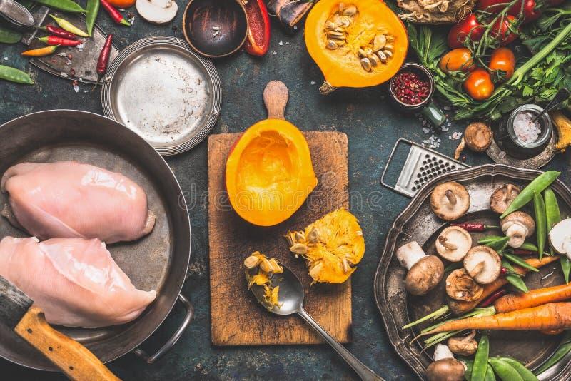 Förberedelsen med pumpa, grönsaker och champinjoningredienser med det fega bröstet i matlagning lägger in, mörk lantlig bakgrund royaltyfri foto