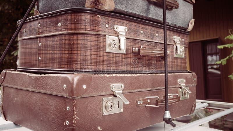 Förberedelser för lopp Gamla resväskor som överst staplas av de på taket av en tappningbil royaltyfria foton