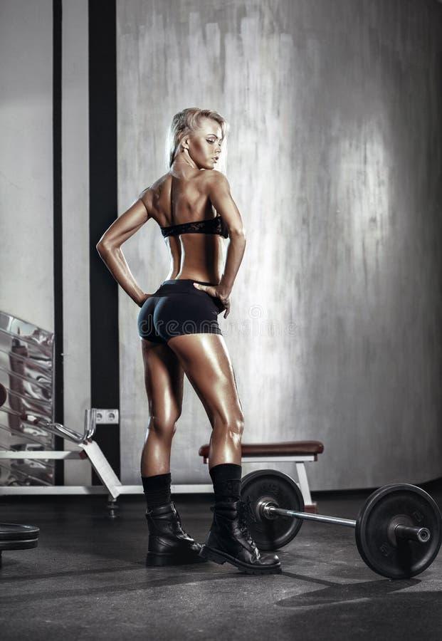 Förbereder sig den blonda flickan för kondition för att öva med skivstången i idrottshall fotografering för bildbyråer