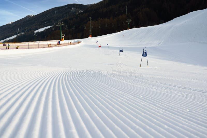Förberett skidar lutningen med jätte- slalomportar royaltyfria foton