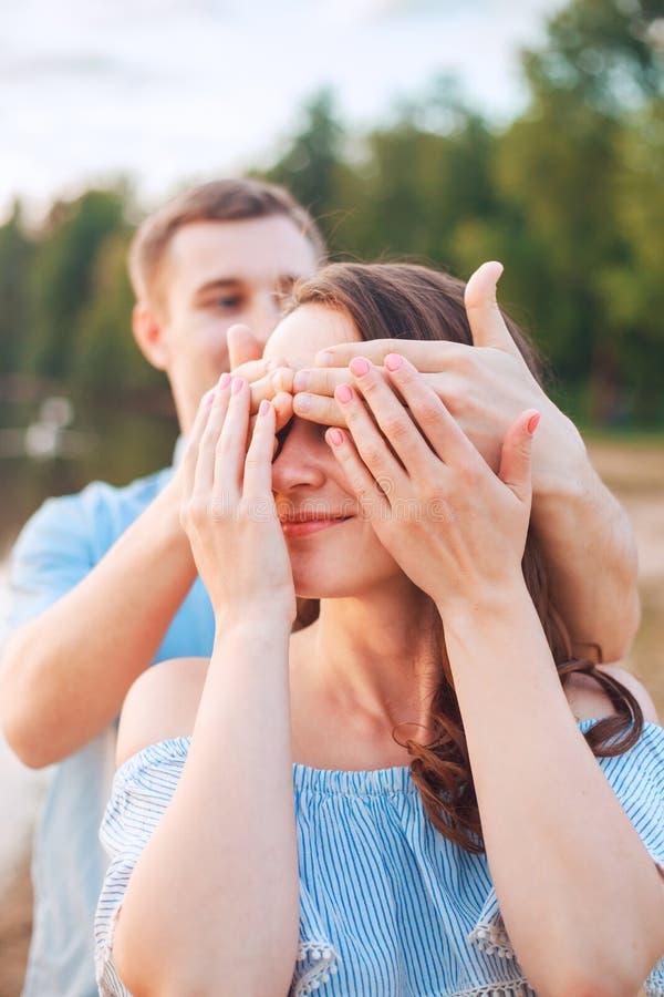 Förbindelseförslag på solnedgång den unga mannen gör ett förslag av trolovning till hans flickvän på stranden royaltyfri foto