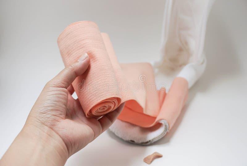 Förbinder den övre sjuksköterskahanden för slutet med för inpackning spjälkar för att såra behandling royaltyfria bilder
