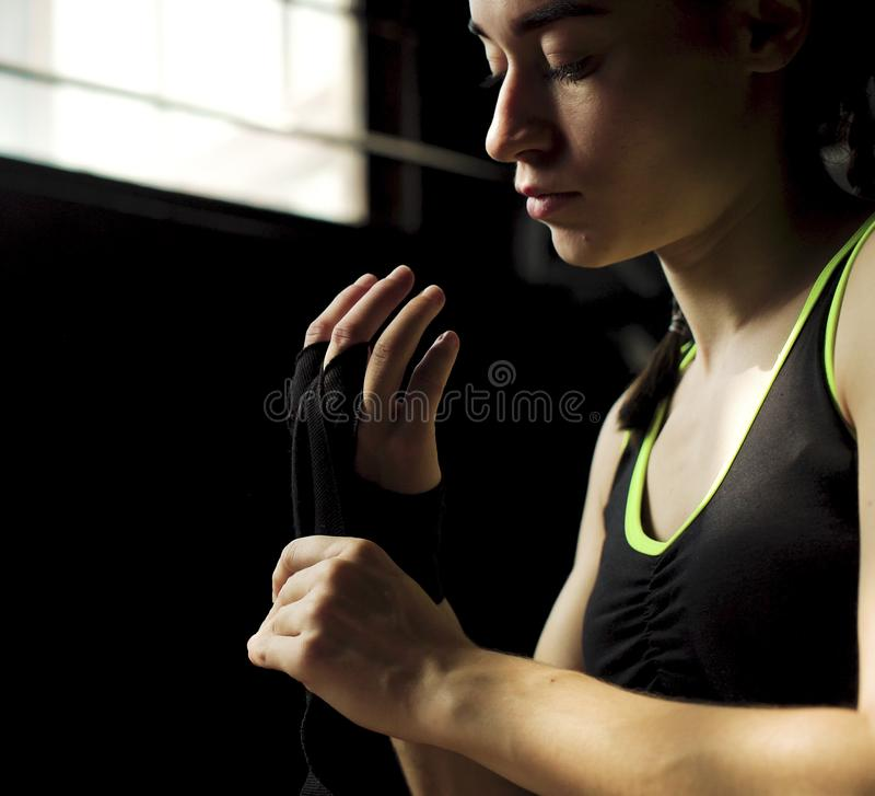 Förbinder den färdiga kvinnan för closeupen som slår in händer med, bandet som förbereder sig för att boxas utbildning royaltyfri fotografi