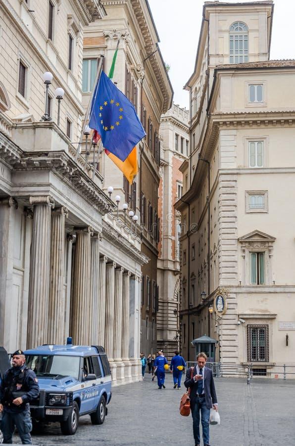 Förbipasserandeaffärsman i en dräkt och polisen nära bilen i borggården mellan de historiska byggnaderna med fönster till smattra royaltyfri fotografi