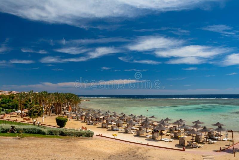 Förbise stranden och slags solskydd på Calimera Habiba Beach Resort royaltyfria bilder