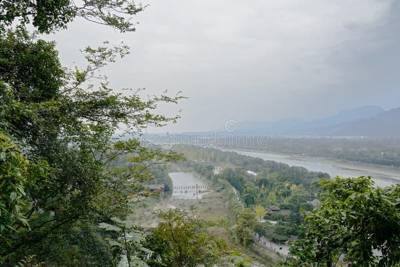 Förbise till flodstrandlandskapet i molnig och dimmig vinter after arkivbild