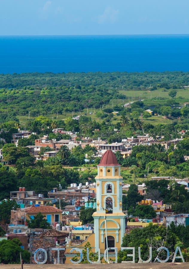 Förbiser den koloniala karibiska staden för den tropiska sjösidan med den klassiska byggnad och kyrkan, Kuban, Amerika royaltyfri bild